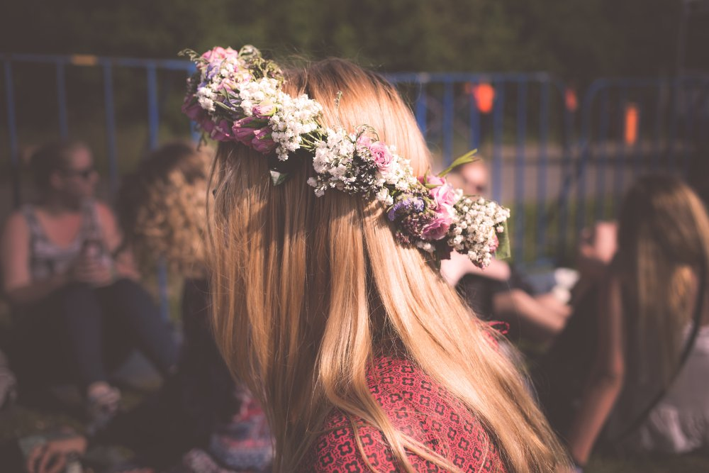 Long haired woman wearing crown of flowers in park