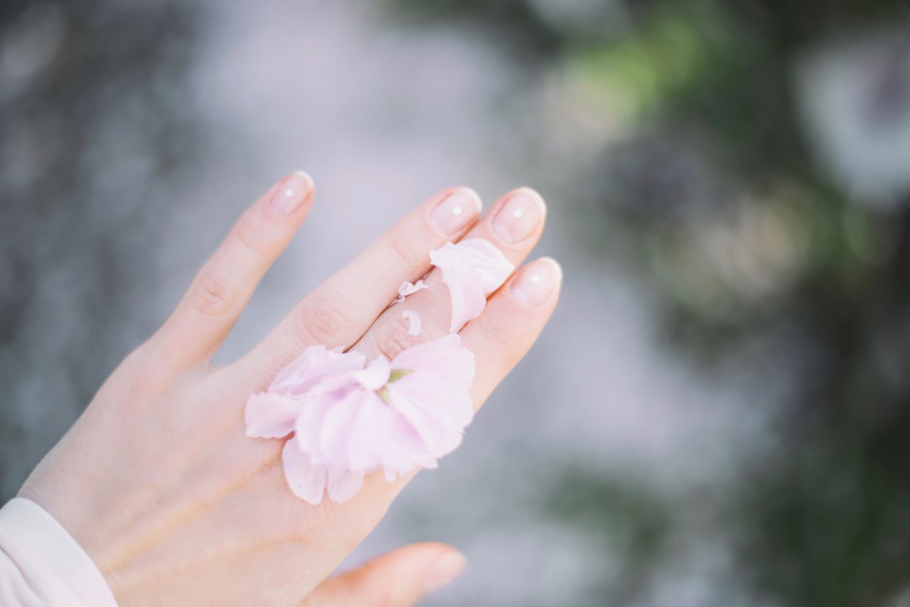 Manicured hand with white flower