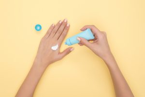 Close up of female hands on yellow background using hand moisturiser in blue tube
