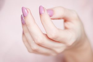 Close up of female hand with pink nail polish