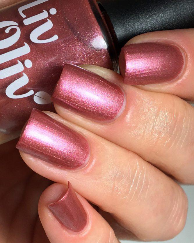 Close up female hand holding LivOliv 'Wine Me Dine Me' nail polish